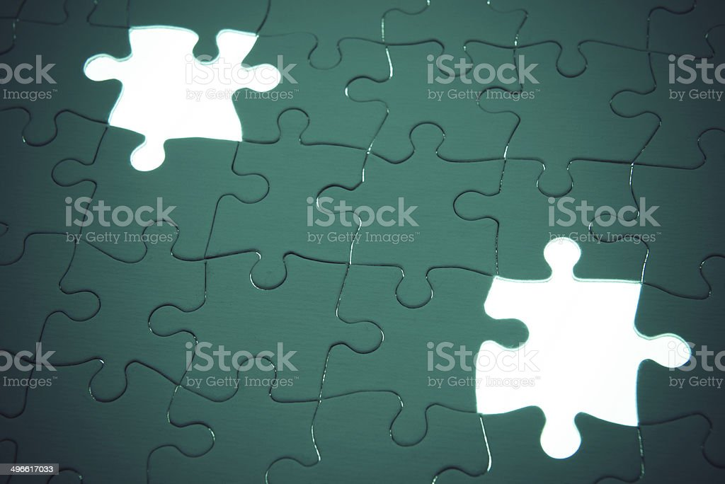 Colorful vivid green puzzle with missing pieces on a light box.