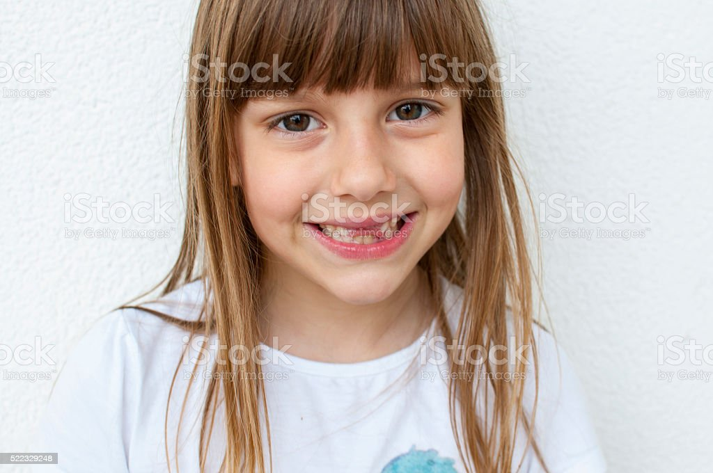 Cute little girl with missing teeth and posing for camera.