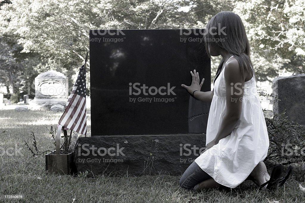 Young girl kneeling at cemetary stone with flag