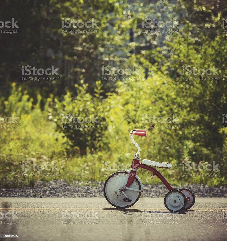 A child\'s tricycle sits in the middle of a country road on a Summer...