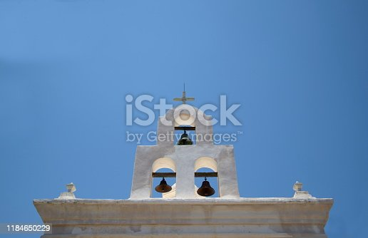 Church bells in an adobe bell tower against a clear blue sky near tuscan arizona reflects the pueblo architecture prevalent in the American southwest