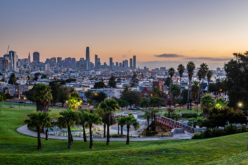 The sun rises over the San Francisco skyline from Mission Dolores Park.