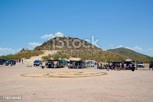 tucson, arizona, use - july, 17, 2019: The Mission San Xavier del Bac parking lot where they are holding a flea market under the hot sun and several tourist are climbing the small mountain in the background