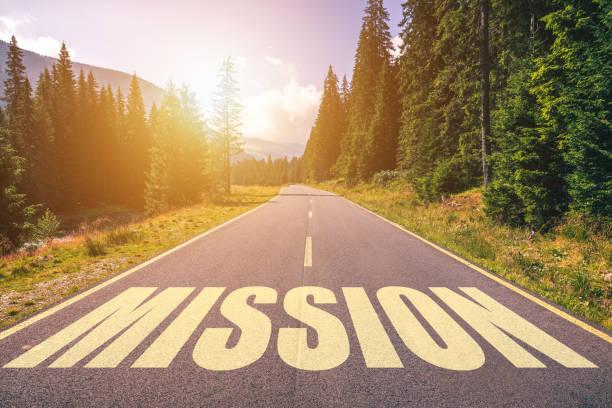 山の道に書かれたミッションの単語 - 決意 ストックフォトと画像