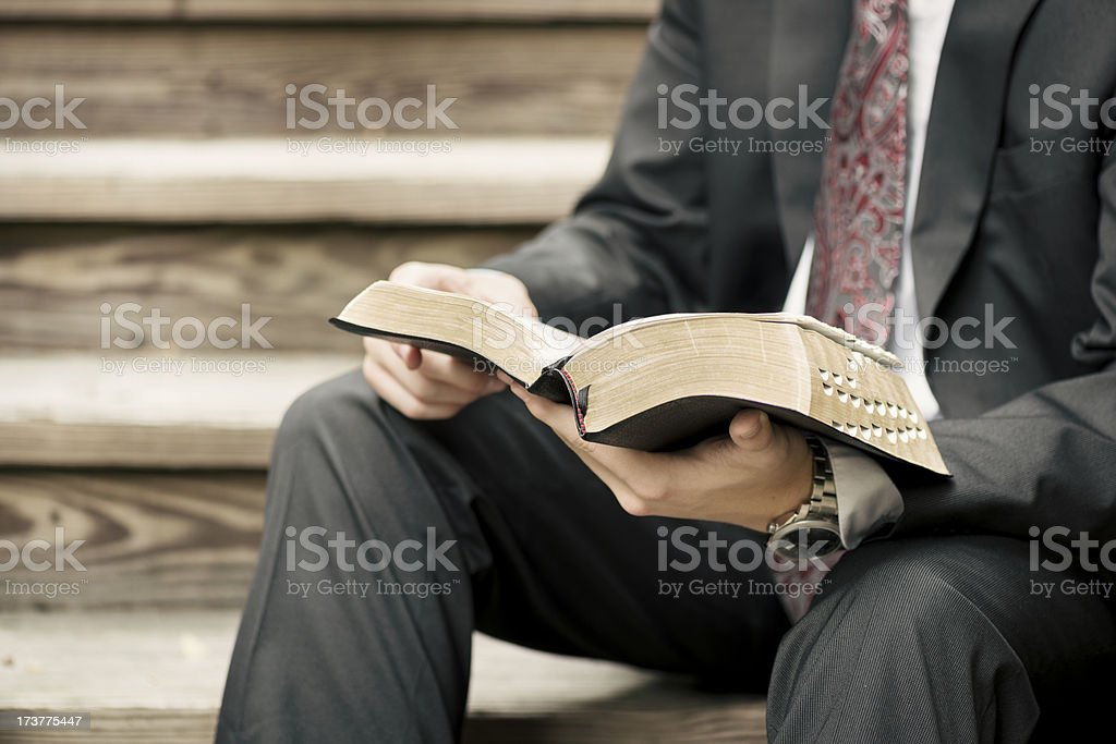 Missionary Sitting on Stairs Reading from the Scriptures stock photo