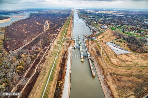 A lock on a man-made tributary diverting water from the natural river to the east  to overcome the annual variances in water depth on the river in order to maintain the shipping trade along the Mississippi River in the central United States.  This aerial view is just outside of St. Louis, Missouri on the Illinois side of the river.