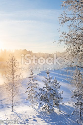 Mist over freezing river on a sunny cold winter day. Trees covered with frost and snow. Eastern Finland.