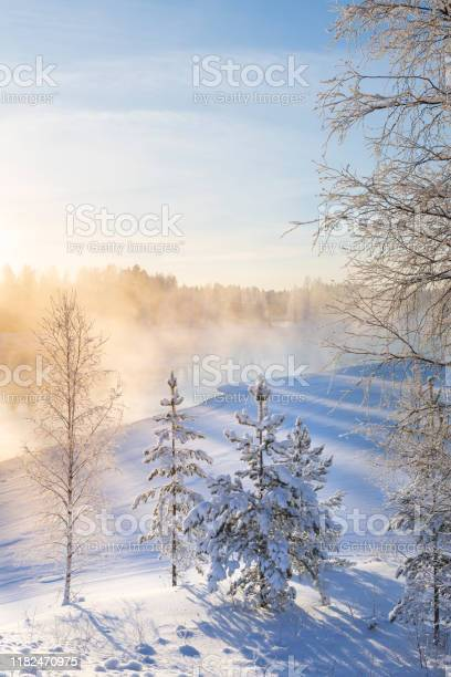 Photo of Mist over freezing river on a sunny cold winter day