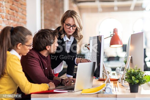 Shot of three colleagues in front of the laptop at their workplace
