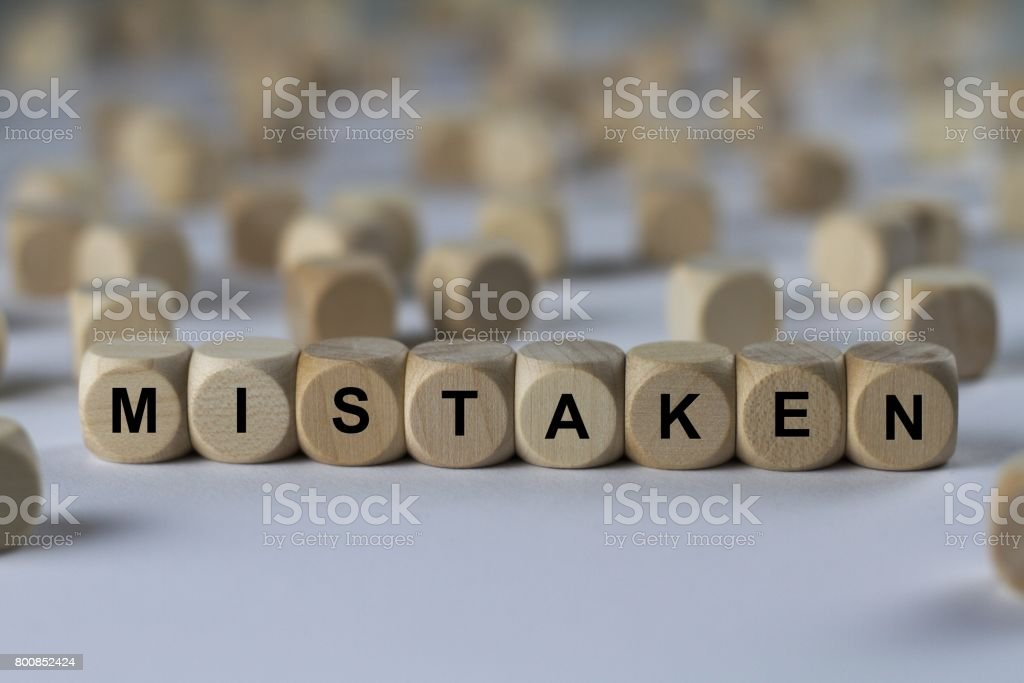 mistaken - cube with letters, sign with wooden cubes stock photo