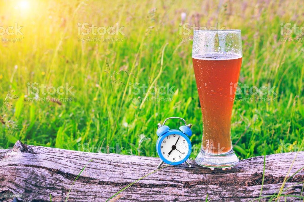 Misted copo de cerveja gelada e um despertador no fundo de grama verde, ao pôr do sol. Hora de fazer uma pausa e beber cerveja. Futebol e álcool. - foto de acervo
