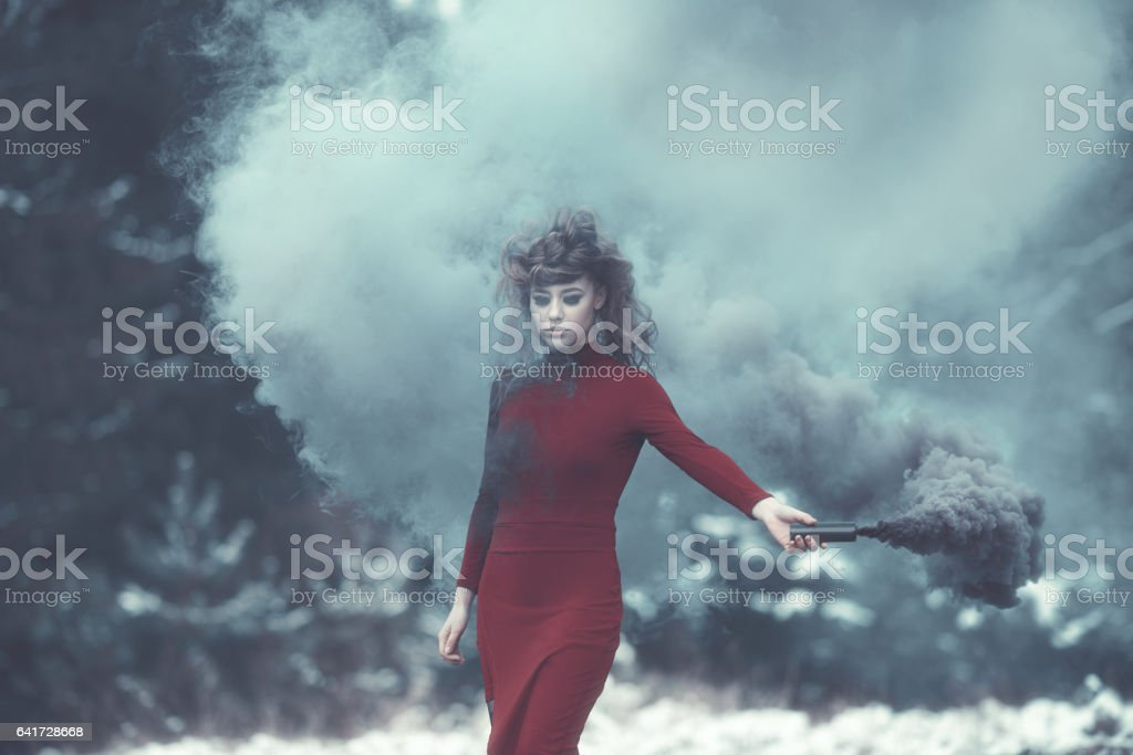 misterious witch with flaming torch stock photo
