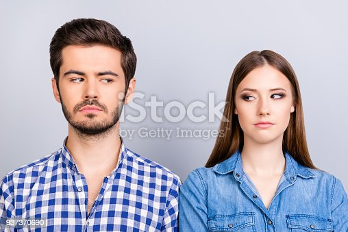 494388938istockphoto Mistrust and cheat problems. Annoyed couple is ignoring each other, but spy each other secretly, they stand on pure background in casual shirts 937370690