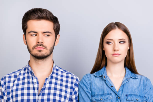 Mistrust and cheat problems. Annoyed couple is ignoring each other, but spy each other secretly, they stand on pure background in casual shirts stock photo