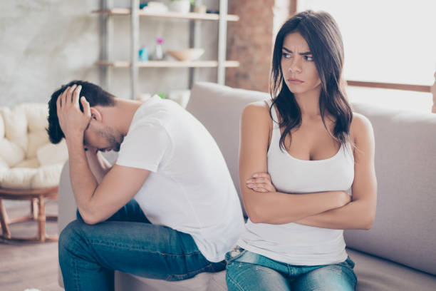 mistrust and cheat problems. annoyed couple is ignoring each other, sitting on the couch upset indoors at home. i am not talking to you! - fighting stock photos and pictures