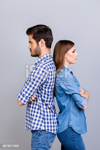 istock Mistrust and cheat problems. Annoyed couple is ignoring each other, standing back to back, wearing casual clothes, with crossed hands on the pure background 937821500