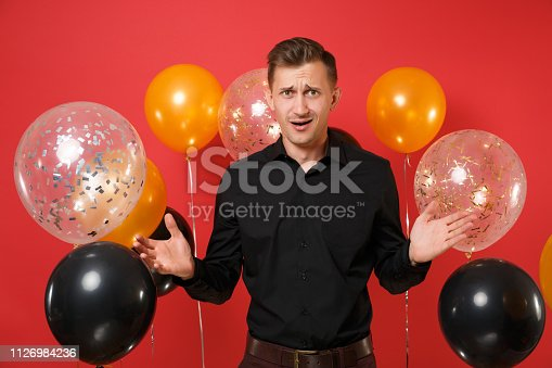 istock Mistrustful perplexed young man in black classic shirt celebrating, spreading hands on red background air balloons. St. Valentine's, Women's Day, Happy New Year, birthday mockup holiday party concept. 1126984236