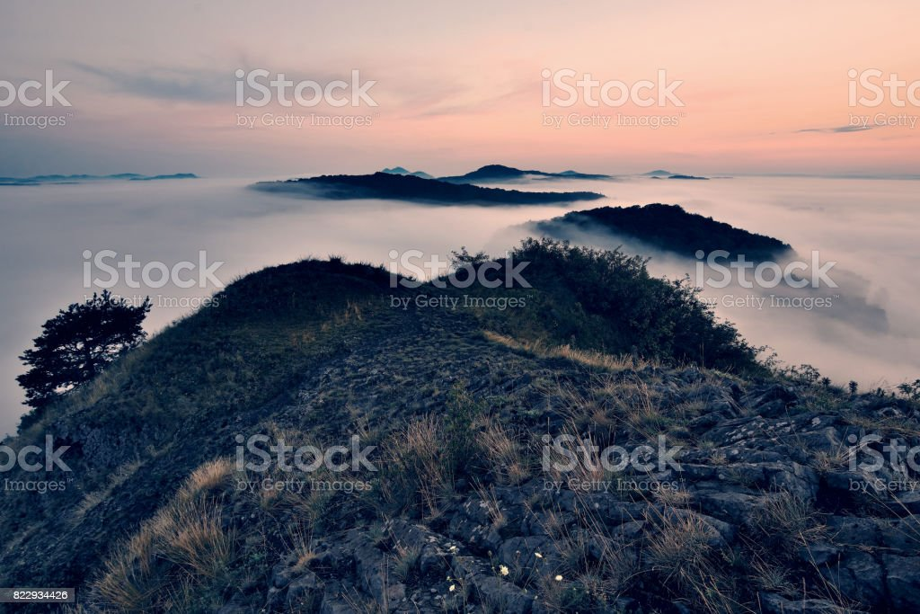 Misty dreamy landscape at beginning of autumn. Heavy mist  on meadow, hills and town at horizon. stock photo