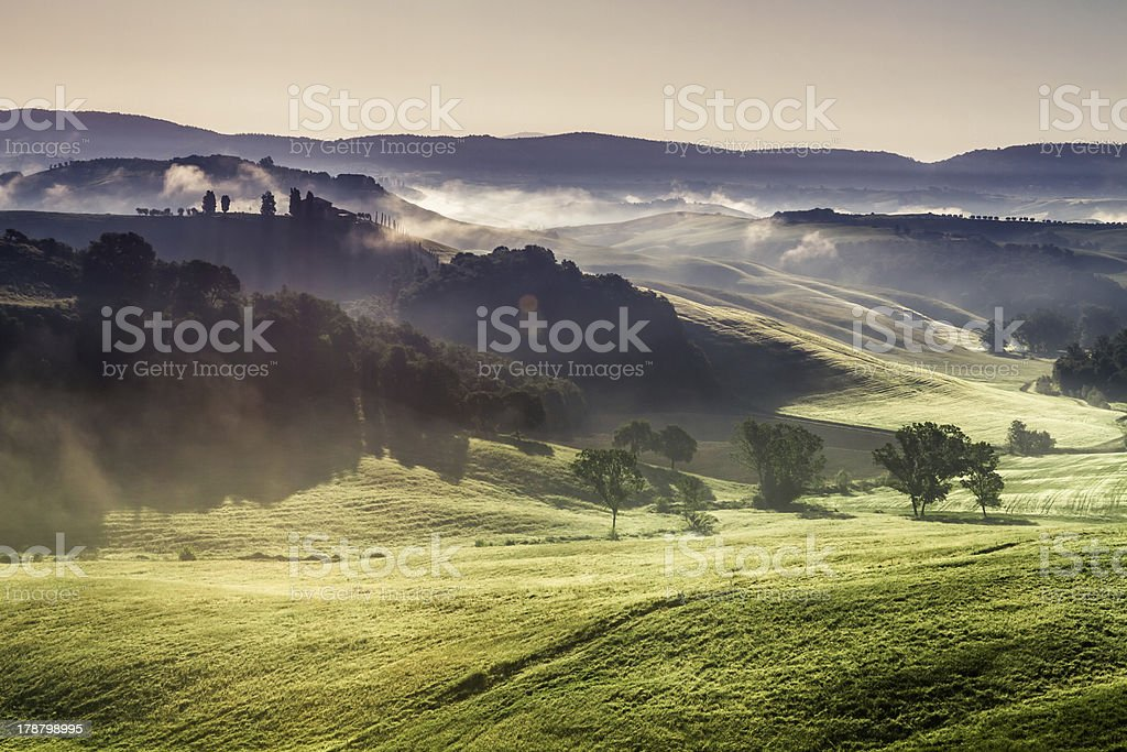 Misty hills and meadows in Tuscany at sunrise stock photo