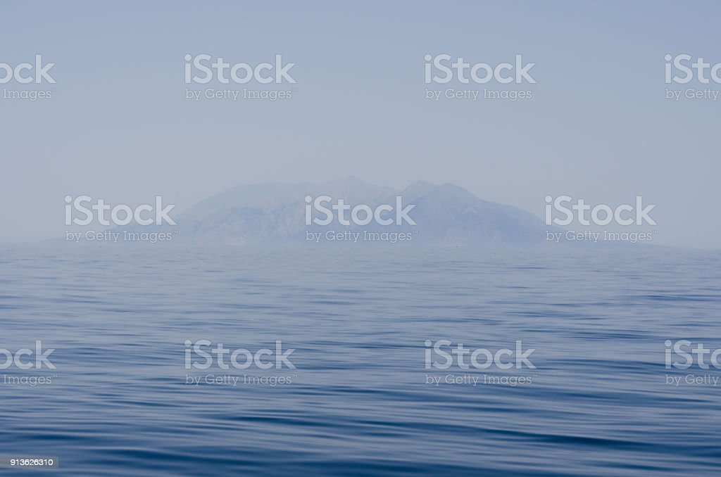 Misty island appearing over troubled water stock photo
