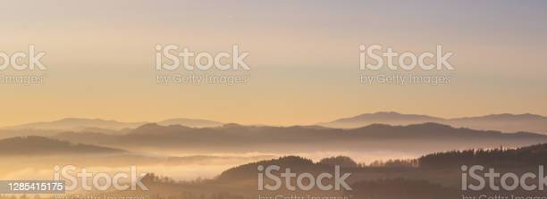 Photo of misty landscape at sunset, mountains rising from clouds of fog, clear sky