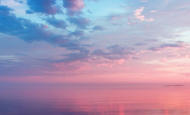misty lilac seascape with pink clouds - skies stock photos and pictures