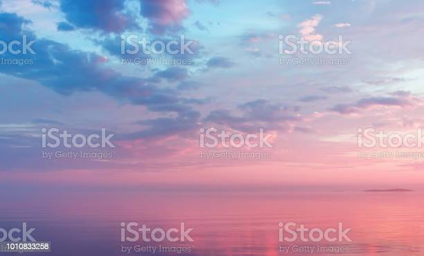 Misty lilac seascape - pink and blue clouds over the water of calm Lake Onega and the small island in the White Nights season - Russia, Republic of Karelia. Soft focus.