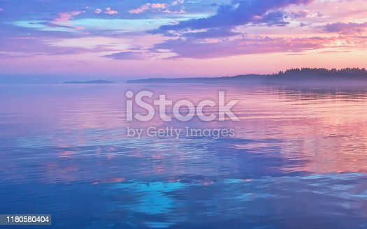 Misty seascape - calm water surface of the lake reflects lilac sky with pink and blue clouds after sunset. White nights season in the Republic of Karelia, Russia. Blur filter, space for copy.