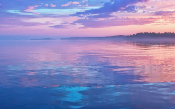 Misty Lilac Sunset Seascape With Sky Reflection Misty seascape - calm water surface of the lake reflects lilac sky with pink and blue clouds after sunset. White nights season in the Republic of Karelia, Russia. Blur filter, space for copy. republic of karelia russia stock pictures, royalty-free photos & images