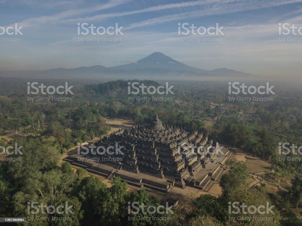 A misty morning at the Borobudur Temple with volcanoes in the background stock photo