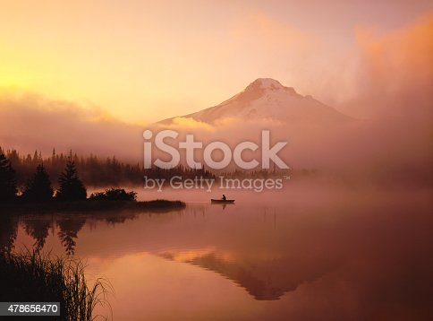 Spring morning with clearing fog at Trillium Lake also Mt. Hood and lone fisherman in canoe reflects in the calm waters, Oregon