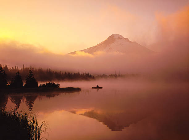 Misty morning, canoe, with the reflection of  Mt. Hood, OR Spring morning with clearing fog at Trillium Lake also Mt. Hood and lone fisherman in canoe reflects in the calm waters, Oregon mt hood stock pictures, royalty-free photos & images