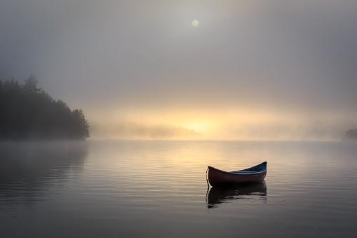 Peaceful misty lake shot of canoe.