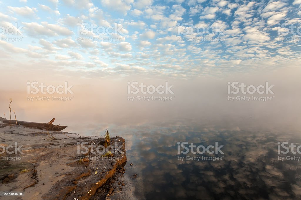 misty morning on the river and clouds reflected in water stock photo
