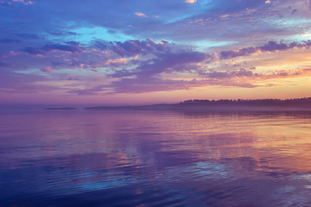 Misty Purple Seascape At Sunset In The White Nights Season Amazing night seascape - calm water surface reflects colorful dramatic sky with purple clouds and mist floating on the horizon at sunset. White Nights season. Republic of Karelia, Russia. republic of karelia russia stock pictures, royalty-free photos & images