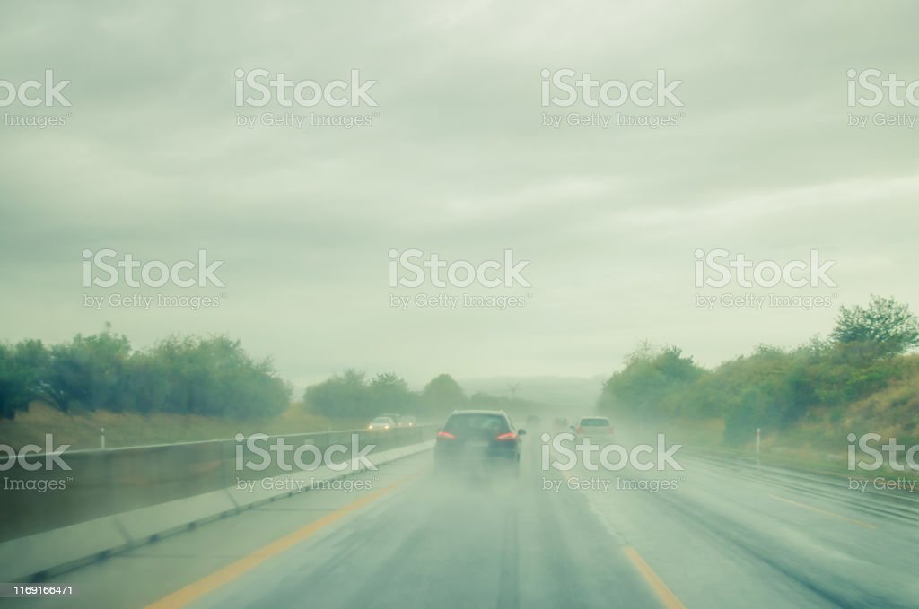 cars driving in rainy weather on wet and slippery road