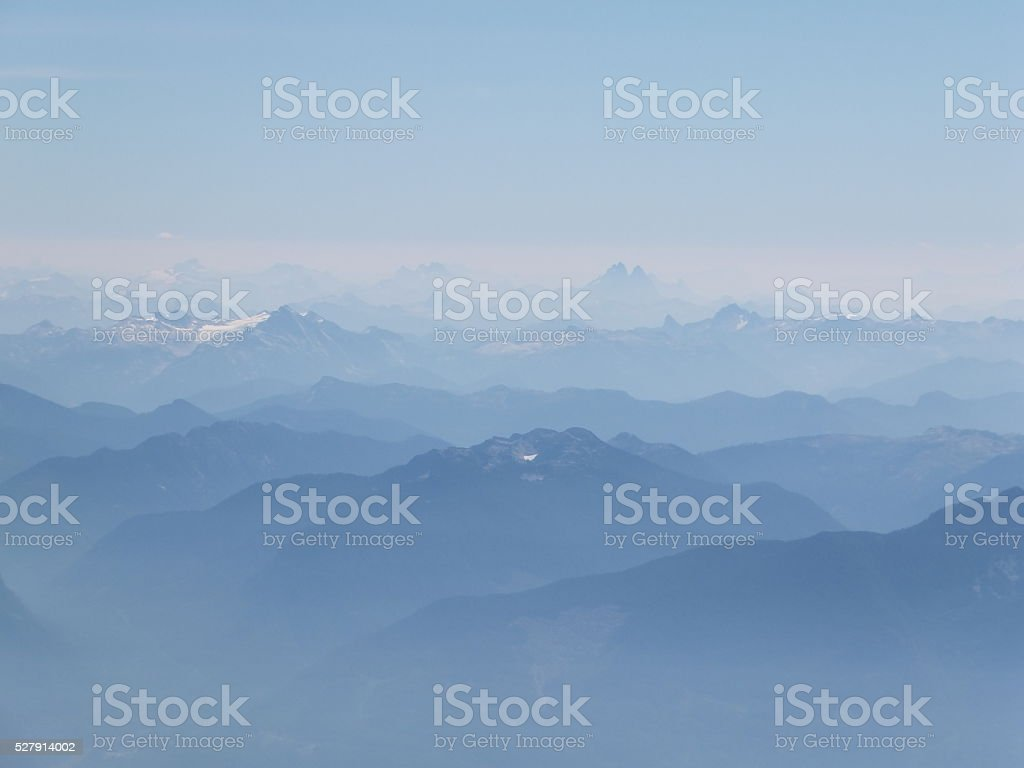 Misty snow covered mountain peaks stock photo