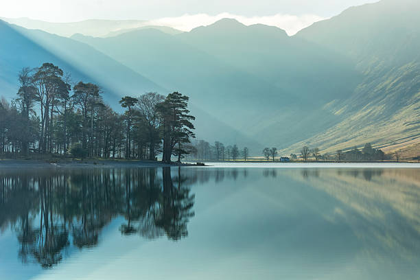 Misty Sunbeams With Reflections Of Trees In Lake With Mountains Beautiful sunbeams shining through a thin layer of mist with calm reflections of trees in the lake at Buttermere in the English Lake District. Taken on a spring morning, the green colours are starting to appear on the mountain sides. english lake district stock pictures, royalty-free photos & images