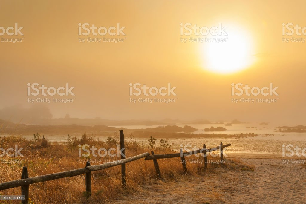 Misty sunset on the beach stock photo