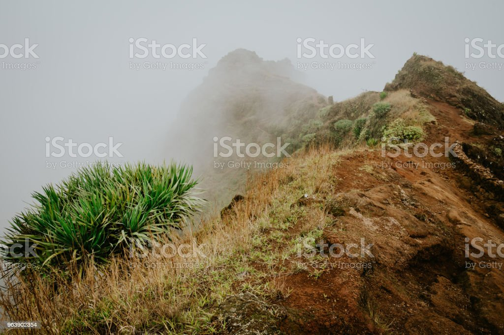 Misty trail leads along the mountain ridge. Path and steep slopes hidden in the fog. Santo Antao Cape Verde - Royalty-free Adventure Stock Photo