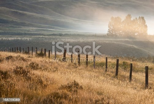 A misty valley with rustic wooden fence. Alberta, Canada. Rural scenic. Horizontal colour landscape. Location is Glenbow Ranch Provincial Park just north of Calgary. This region has a history of mining and ranching. Beautiful prairie grasses and a variety of plant and animal life thrive here. Scenic or landscape image of a very beautiful park and place just outside Calgary city limits. Nobody is in the image.