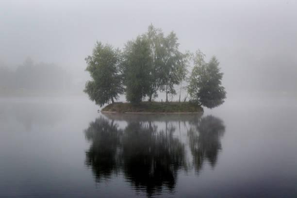 misty sehr kleine insel am nebligen see im morgenlicht stunden - die toteninsel stock-fotos und bilder