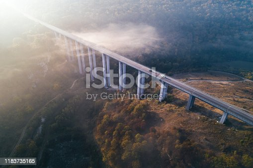 istock Mistyc Aerial view of a highway on a viaduct, high tech engeneering construction, ochre colored landscape and low clouds in the sky. 1183735165