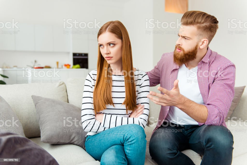 Misunderstanding people person concept. Puzzled annoyed handsome irritated boyfriend trying to figure out the reason of resentment. Pretty girl doesn't want to listen to boyfriend sitting crossed arms stock photo