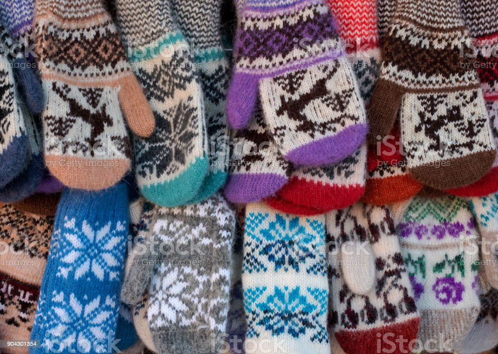 Mittens on the winter Christmas market. Multi-colored knitted woolen mittens. stock photo