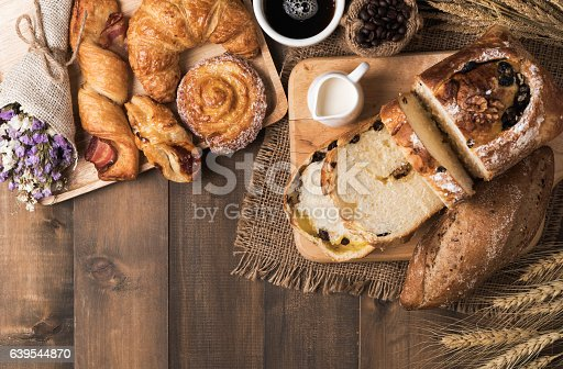 istock Mix baked bread and wheat on wood table background. 639544870