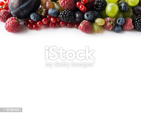 Mix berries on a white background. Ripe red currants, grapes, blackberries, blueberries, raspberries and plums on white background. Top view. Fruits with copy space for text. Mix berries and fruits. Background berries and fruits. Various fresh summer fruits.