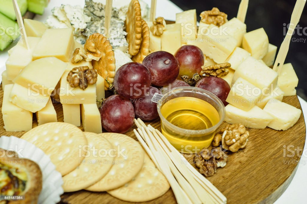 Mix cheese on wooden board with grapes. Front view. stock photo