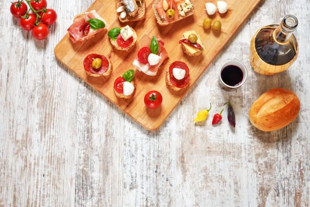 mischung aus vorspeisen / snacks. mediterrane tapas oder antipasti auf einem rustikalen holztisch. - mini weinflaschen stock-fotos und bilder