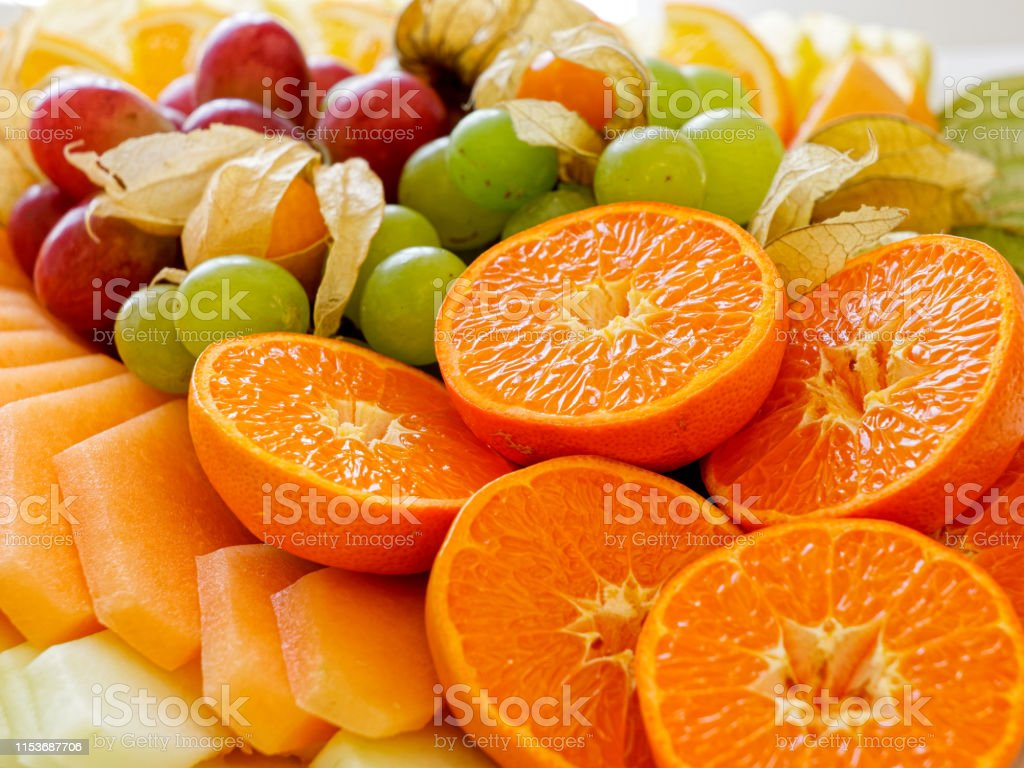 Mix of arranged freshly cut tropical and citrus fruit.